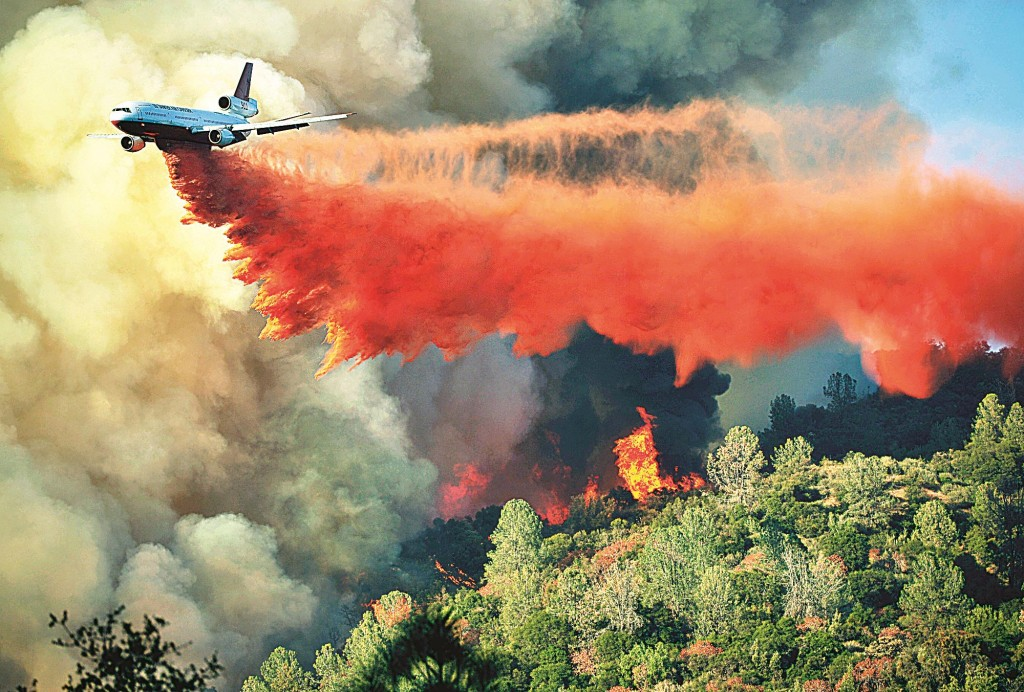 An air tanker drops fire retardent on a fire which was burning on a ridge northeast of Oakhurst, Calif. (AP Photo/The Fresno Bee, Eric Paul Zamora)