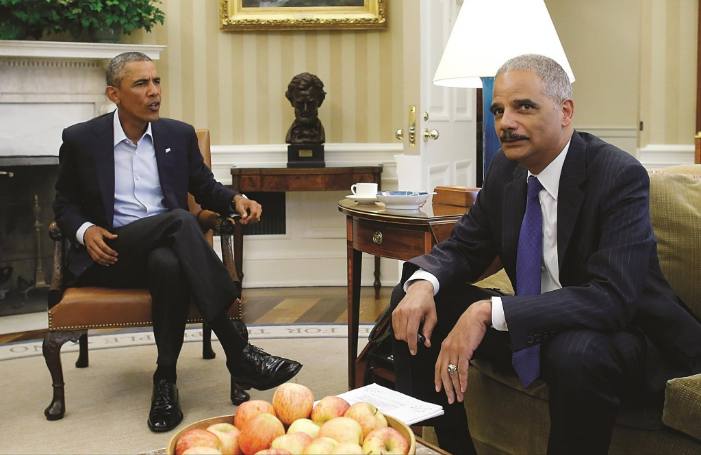 President Barack Obama speaks with Attorney General Eric Holder as news photographers photograph their meeting regarding the fatal police shooting of Michael Brown in Ferguson, Missouri, Monday, during their meeting in the Oval Office at the White House in Washington.  (AP Photo/Charles Dharapak)