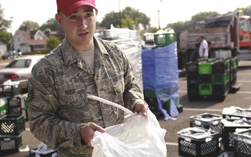 A member of the Ohio Air National Guard carries a bag of water to a nearby car, Sunday, at Woodward High School in Toledo, Ohio.  (AP Photo/Haraz N. Ghanbari)
