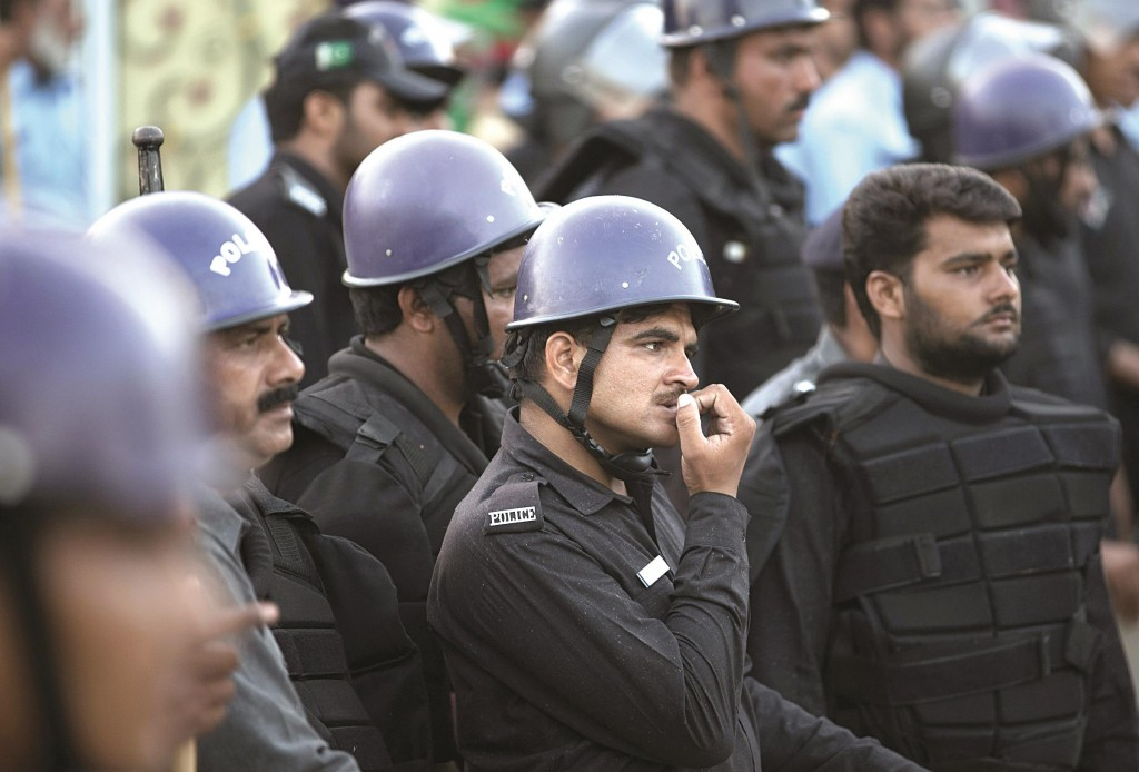 Pakistani police officers wait to stop marchers arriving in Islamabad, Pakistan, Tuesday. (AP Photo/B.K. Bangash)