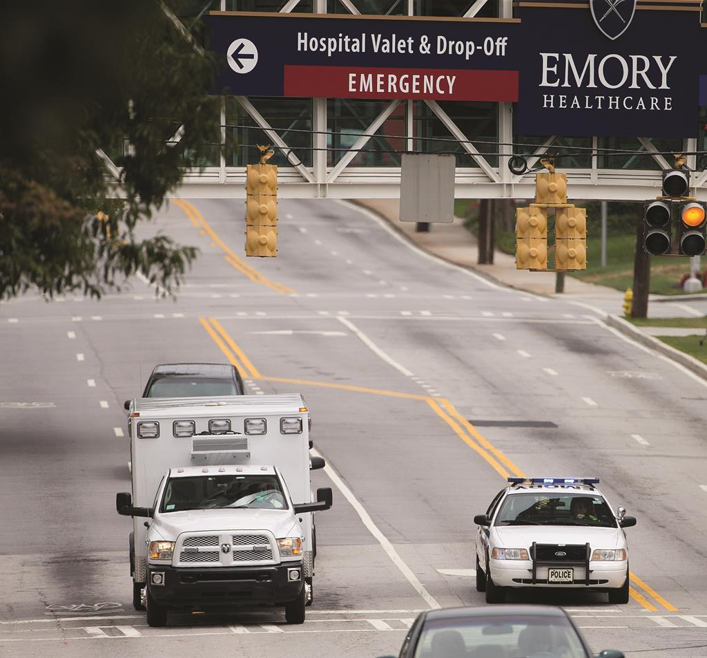 An ambulance arrives at Emory University Hospital in Atlanta, transporting an American who was infected with the Ebola virus. (AP Photo/David Goldman)