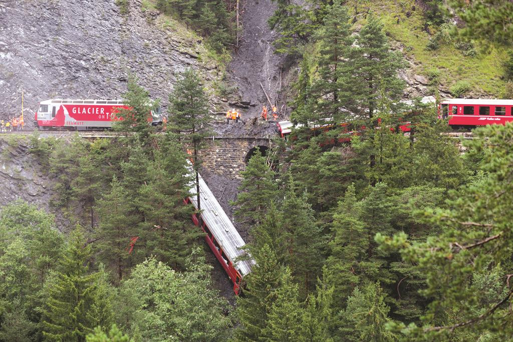 A derailed passenger train is pictured near Tiefencastel, Switzerland, Wednesday. (AP Photo/Keystone, Arno Balzarini)