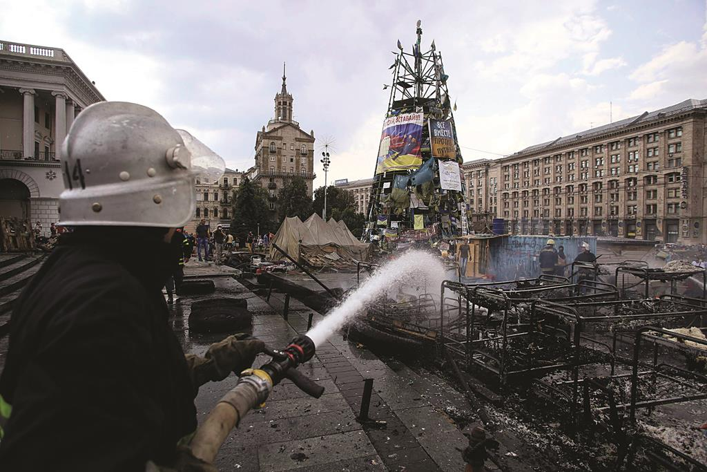 A firefighter extinguishes barricades set on fire by protesters at Independence Square in Kiev. Tensions continued on Kiev's Independence Square, the scene of street protests that toppled a Moscow-backed president in February, as protesters still camped there clashed with city workers who tried to clear away their tents. (REUTERS/Konstantin Grishin)