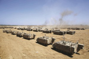Armored Personnel Carriers (APC) park at a staging area at an unspecified location near the Israeli border with the Gaza Strip, Wednesday.  (EPA/ABIR SULTAN)