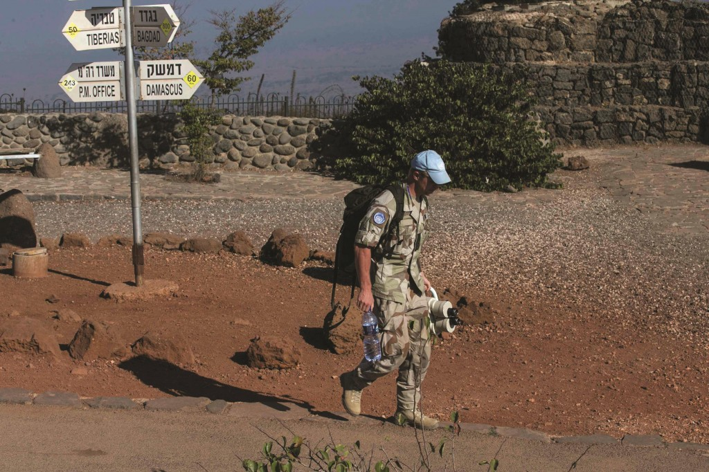 A member of the United Disengagement Observer Force (UNDOF) carries binoculars at Mount Bental, an observation post in the Golan Heights that overlooks the Syrian side of the Qunietra crossing Sunday. (REUTERS/Baz Ratner)