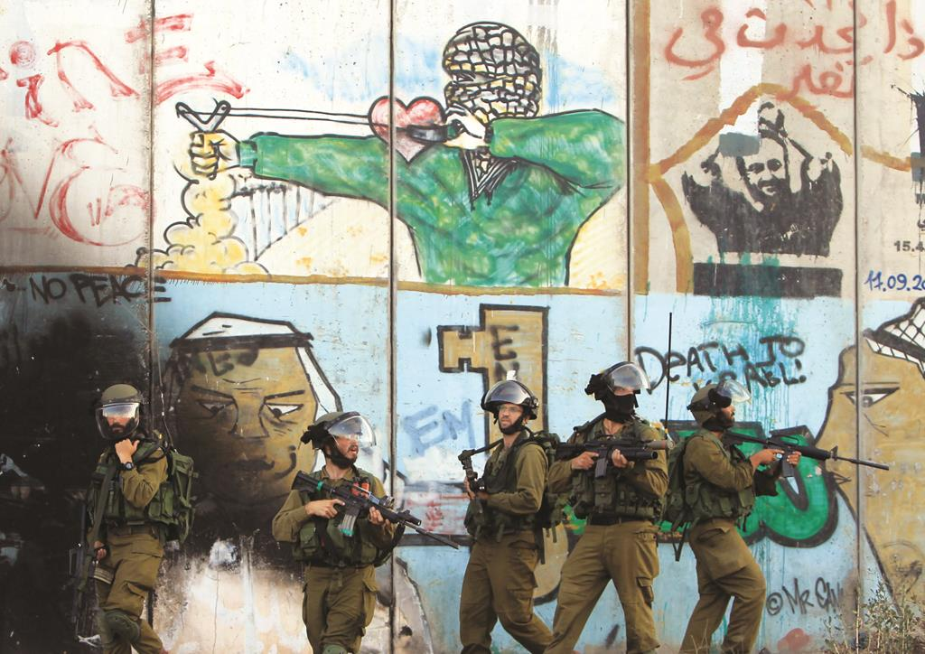 Israeli soldiers stand in front of the graffiti-covered wall during clashes with Palestinian stone throwers at the Israeli Qalandiya checkpoint between Ramallah and Yerushalayim. (ABBAS MOMANI/AFP/Getty Images)