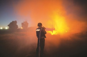 An Israeli firefighter extinguishes fire after rockets fired by Palestinian terrorists from the Gaza strip hit a field near the southern Israeli city of Sderot on Wednesday. (MENAHEM KAHANA/AFP/Getty Images)