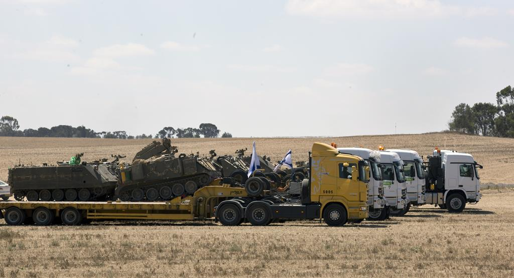 Israeli APCs (Armored Personnel Carriers) on flat bed trucks as they are readied for transport from a staging area near the Gaza Strip border, inside southern Israel, Sunday.  (EPA/JIM HOLLANDER)