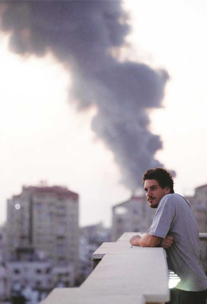 This photo taken in August, 2014 shows Associated Press video journalist Simone Camilli on a balcony overlooking smoke from Israeli strikes in Gaza City.  (AP Photo/Lefteris Pitarakis)