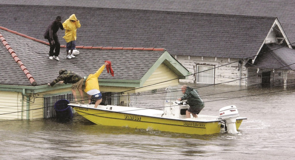 Residents are rescued from their rooftop after Hurricane Katrina hit, causing flooding in their New Orleans neighborhood, Monday morning, Aug. 29, 2005. Officials called for a mandatory evacuation of the city, but many residents remained in the city.  (AP Photo/Eric Gay)