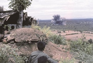 People watch smoke rise from an American air strike nearby, in the countryside around Phnom Penh, Cambodia, July 1973. On August 14 the bombing came to a halt. (AP Photo/Costo)