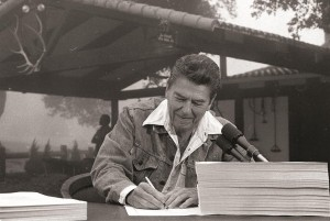 President Ronald Reagan signs the largest tax cut bill in U.S. history at his ranch near Santa Barbara, Calif., in 1981.  (AP Photo/Charles Tasnadi)