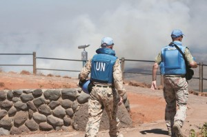 U.N. soldiers seen as smoke rises near Quneitra Crossing as it was seen from the Golan Heights on Wednesday. (Flash90)