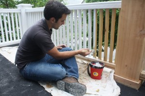 Mike Puma, 24, paints the porch railing of his Buffalo, N.Y., home on June 4, 2014. Puma bought his home for $1 in February, and is slowly making it habitable. It's taken a lot of time and money to rehab the 99-year-old home, but he wanted to save it from demolition. (Alana Semuels/Los Angeles Times/MCT)