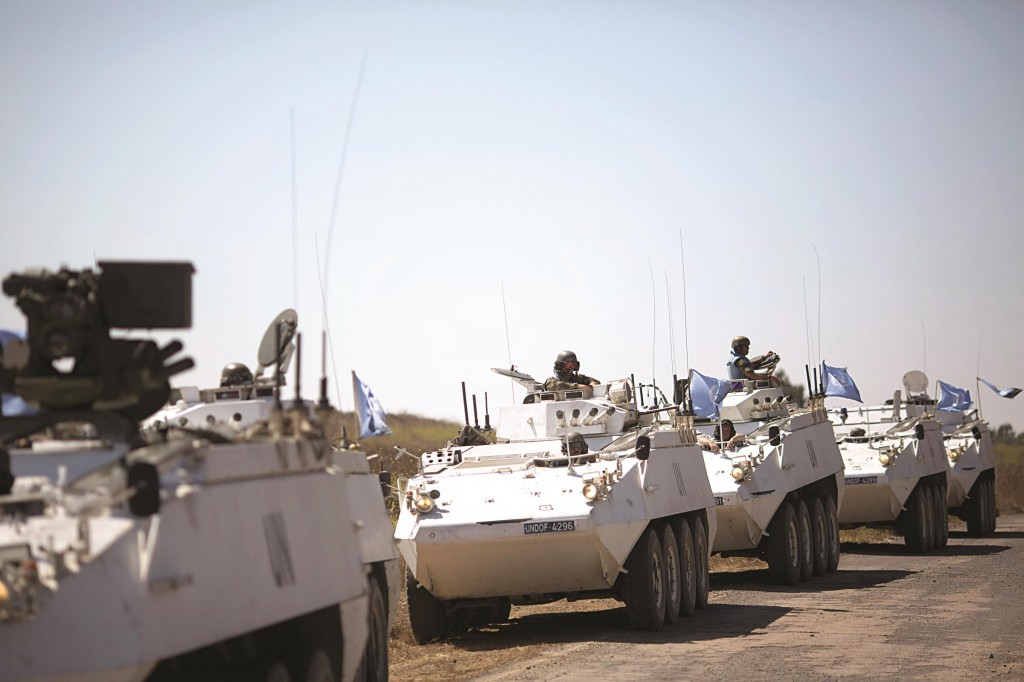 Armored vehicles from the UN peacekeepers of the United Nations Disengagement Observer Force, also known as UNDOF wait to cross from the Israeli controlled Golan Heights toSyria, Thursday. (AP Photo/Ariel Schalit)