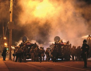 Police wait to advance after tear gas was used to disperse a crowd Sunday, during a protest for Michael Brown who was killed by a police officer last Saturday in Ferguson, Missouri.  (AP Photo/Charlie Riedel)