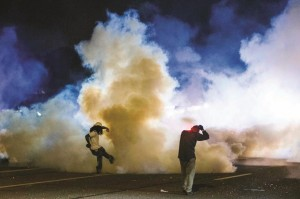 A protester kicks a tear gas canister back towards police after protests in reaction to the shooting of Michael Brown turned violent near Ferguson, Missouri Sunday. (REUTERS/Lucas Jackson)