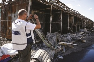 An OSCE member observes damage caused by shelling near the train station in Donetsk, Ukraine, Saturday. Heavy shelling from an unknown source hit a railway station and a nearby market on Friday evening in Donetsk, the largest rebel-held city in eastern Ukraine, an OSCE observer said at the site.  (AP Photo/Mstyslav Chernov)