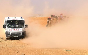 In Sinjar town, a Kurdish Red Crescent ambulance drives past a truck carrying displaced people from the minority Yazidi sect, fleeing violence from forces loyal to the Islamic State. They are making their way towards the Syrian border, on the outskirts of Sinjar mountain, near the Syrian border town of Elierbeh of Al-Hasakah Governorate.  (REUTERS/Rodi Said)