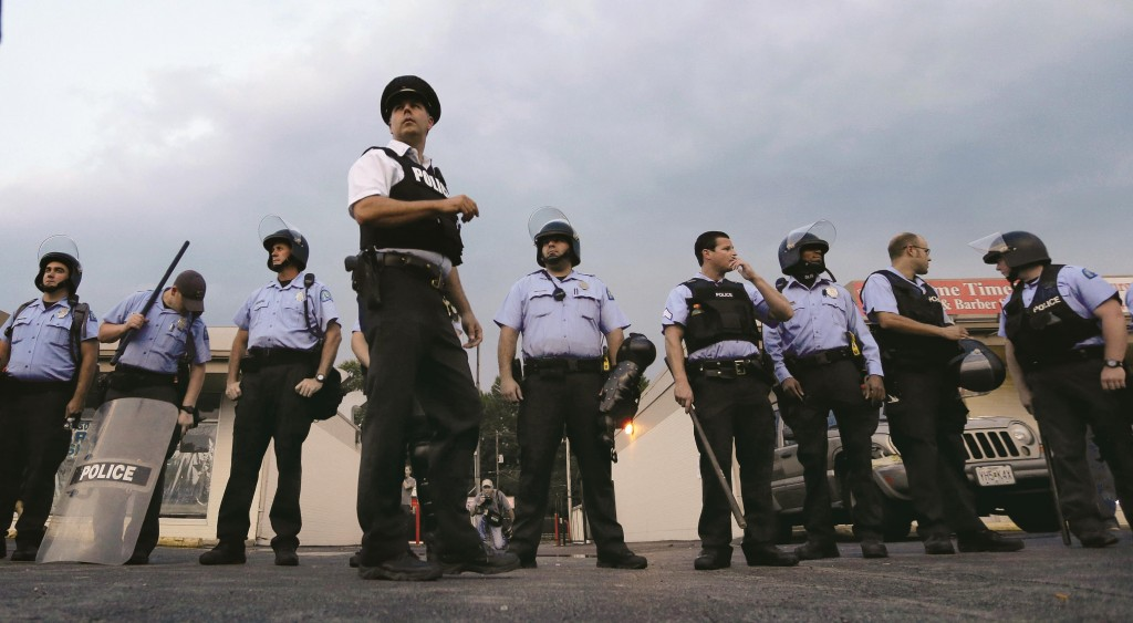 Police in riot gear prepare to take up positions as people protest the police shooting death of Michael Brown a week ago in Ferguson, Mo.  (AP Photo/Charlie Riedel)