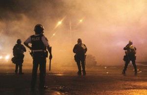 A law-enforcement officer watches Sunday, as tear gas is fired to disperse a crowd protesting the shooting of teenager Michael Brown last Saturday in Ferguson, Mo.  (AP Photo/Charlie Riedel)