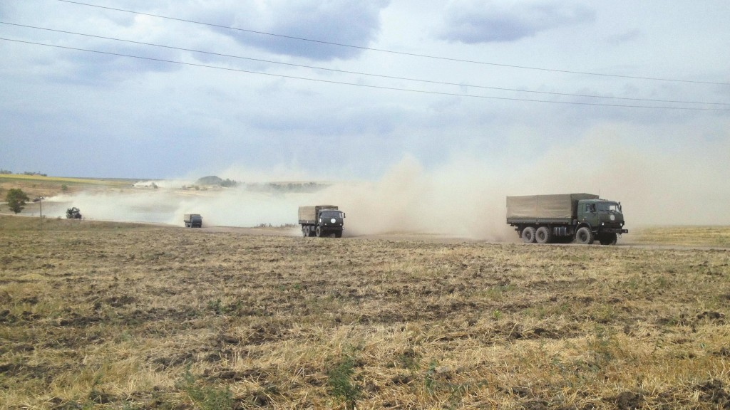 A Reuters reporter saw a column of armored vehicles and troops driving through the Russian steppe Thursday just across the border from a part of Ukraine Kiev says is occupied by Russian troops. The reporter saw a helicopter with  Russian military marking land next to a military first aid tent. (REUTERS/Maria Tsvetkova)