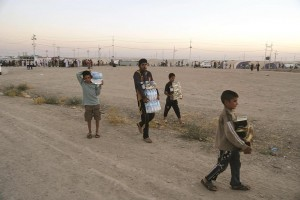 Displaced Iraqi from the Yazidi community carry humanitarian aid at the camp of Bajid Kandala at Feeshkhabour, a town near the Syria-Iraq border, in Iraq.  (AP Photo/ Khalid Mohammed)