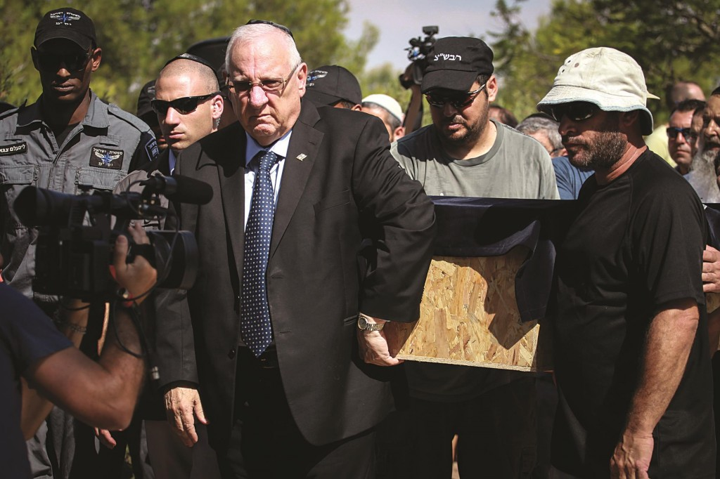 """At the levayah of 4-year-old Daniel Tragerman, Hy""""d. President Reuven Rivlin helps carry the aron at the Hevel Shalom Cemetery in southern Israel on Sunday. (Hadas Parush/Flash90)"""