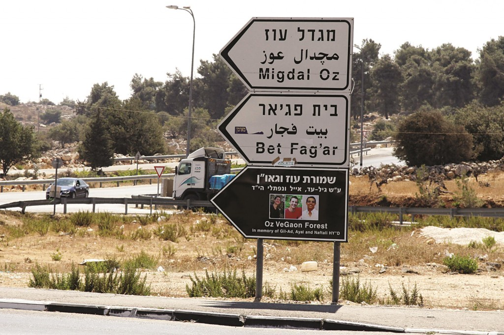 "A road sign with pictures of the three teenagers Nafatli Frankel, Gilad Shaar and Eyal Yifrach, Hy""d, who were abducted and killed by Palestinian terrorists, pointing to an outpost built in their memory near the Gush Etzion junction.  (Gershon Elinson/FLASH90)"
