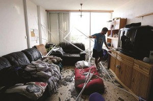 An Israeli surveys the damage to his apartment after a rocket, fired from Gaza, struck a nearby house in the southern coastal city of Ashkelon on Tuesday. (REUTERS/Amir Cohen )