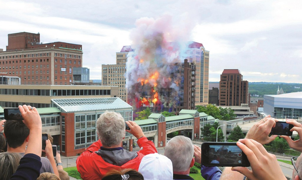 Spectators watch Saturday as the Wellington Annex is imploded to make way for a new Capital Center in Albany. (AP Photo/Times Union, Michael P. Farrell)
