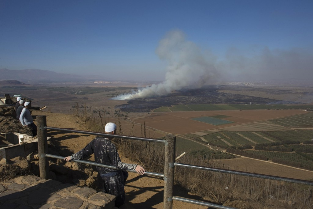 Druze men look at smoke rising on the Israeli side of the  Golan Heights near the border with Syria following fighting near the Quneitra border crossing on Wednesday.  (REUTERS/Ronen Zvulun)