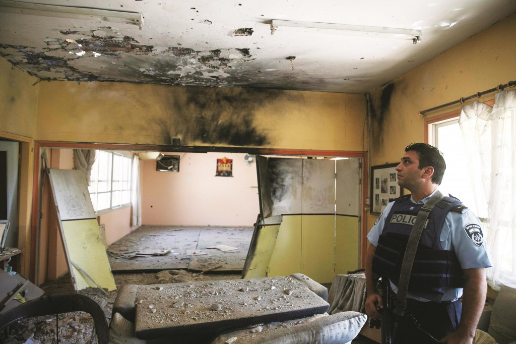An Israeli policeman inspects an empty kindergarten classroom that sustained a direct hit by a mortar fired from Gaza, in the Eshkol region, Thursday.  (REUTERS/Baz Ratner)