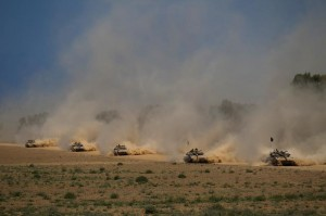 Israeli Merkava tanks seen pulling back from the Gaza Strip, at an unspecified location near the border, Sunday. (EPA/ATEF SAFADI)