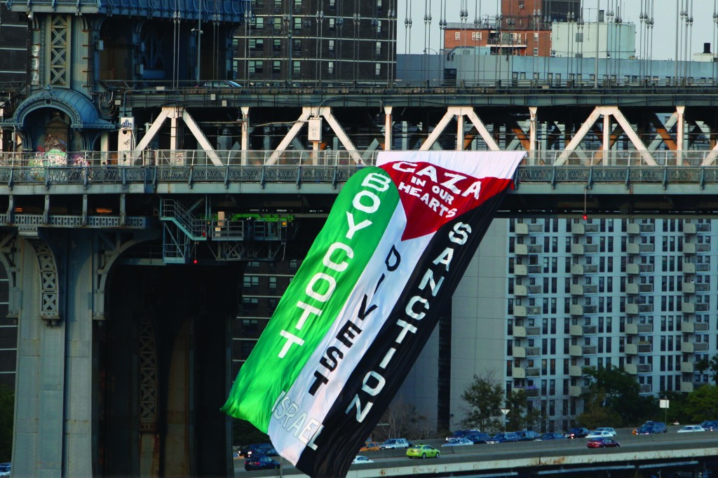 Demonstrators hang a protest flag from the Manhattan Bridge as a pro-Palestinian rally (not pictured) makes its way across the nearby Brooklyn Bridge, Wednesday. (AP Photo/Jason DeCrow)