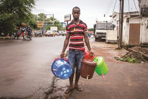 A street trader in Freetown sells plastic hand-washing buckets, as demand for basic sanitation products has boomed during the Ebola crisis. A simple bucket and tap sells for around 10 dollars in the city of Freetown, Sierra Leone, Wednesday. (AP Photo/ Michael Duff)