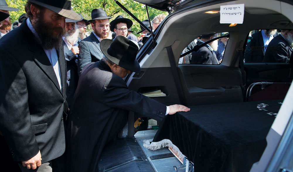 """At the levayah Monday of Rabbi Yosef Raksin, Hy""""d, in Crown Heights, who was shot on Shabbos while in Florida visiting relatives. Police have said the death appeared to result from a robbery and not a hate crime, but they're still investigating. (AP Photo/John Minchillo)"""