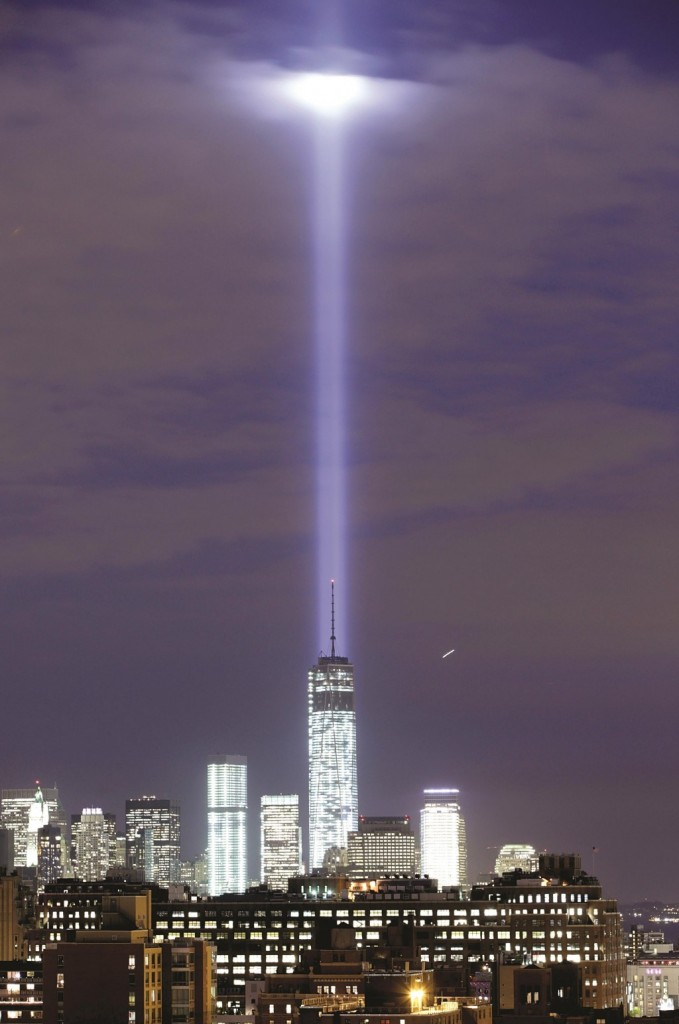The Tribute in Light intersect with still-under construction One World Trade Center as they rise behind the building in last year's 9/11 commemoration. (AP Photo/Kathy Willens)