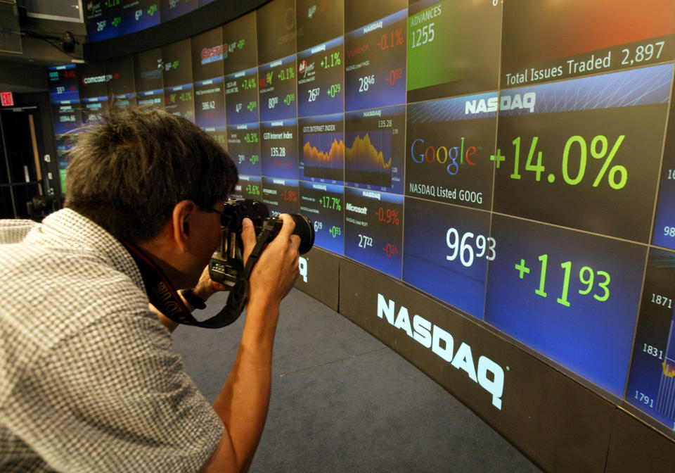 In this Aug. 19, 2004 file photo, a photographer takes pictures of the board at the Nasdaq Marketsite in New York's Times Square shortly after shares of Google started trading. Google's IPO ten years ago launched the company on a trajectory that continues to reshape its business and much of the world in its orbit. (AP Photo/Kathy Willens, File)