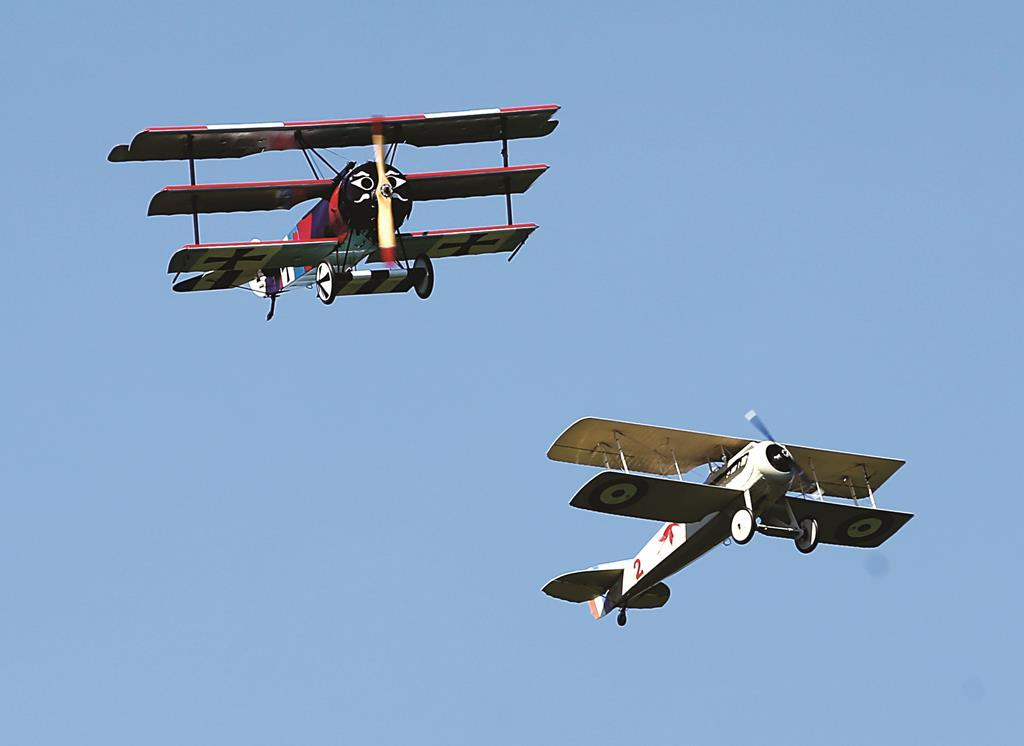 A World War 1-era Fokker DR-1 tri-plane and Spad VII bi-plane, both reproductions, on Sunday perform a dog fight during an air show at the Old Rhinebeck Aerodrome. (AP Photo/Mike Groll)