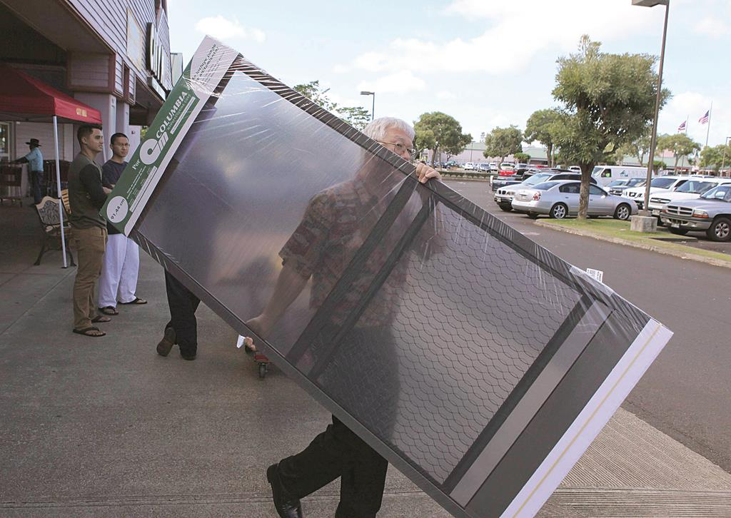 Walton Hong leaves a local hardware store with screen doors to prepare his house as a hurricane and a tropical storm approach the Hawaiian islands, in Mililani, Hawaii, Monday. (REUTERS/Hugh Gentry)