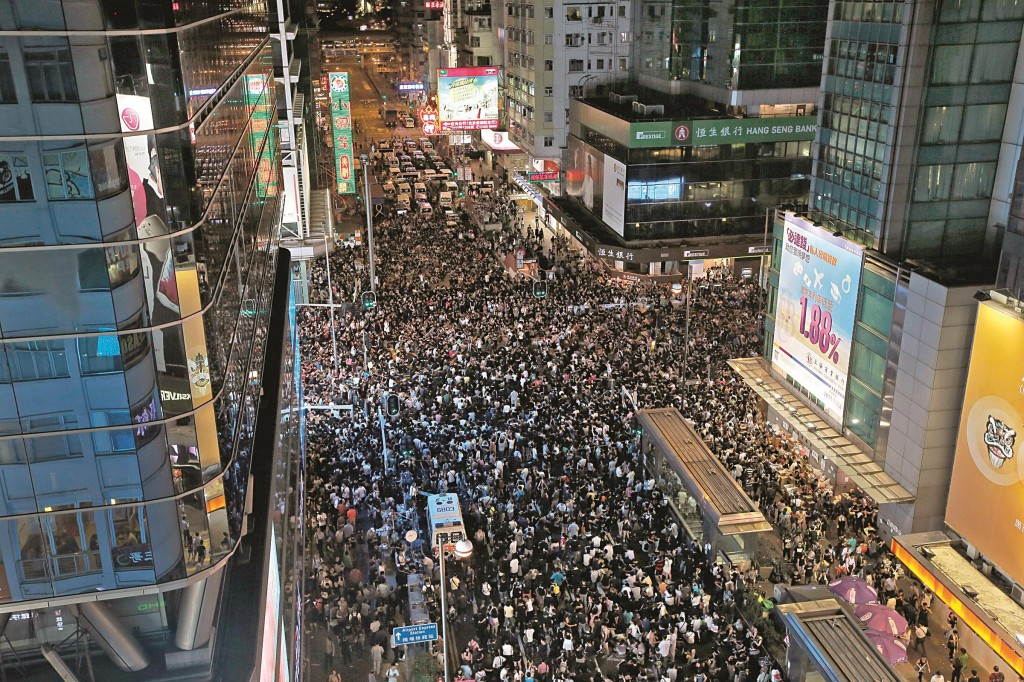 Thousands of pro-democracy protesters gather at Hong Kong's Mongkok district Monday. Protesters expanded their rallies throughout Hong Kong on Monday, defying calls to disperse in a major pushback against Beijing's decision to limit democratic reforms in the Asian financial hub. (AP Photo/Vincent Yu)