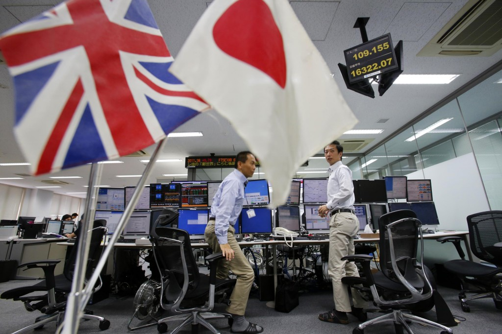 Flags of Britain and Japan are displayed as money traders leave their seats at a foreign exchange dealing company in Tokyo, Friday. The British pound jumped as Scotland voted to stay part of the United Kingdom. (AP Photo/Shizuo Kambayashi)