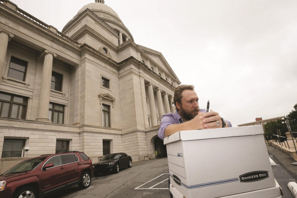 Greg Hale leans on boxes of petitions signed by supporters of a stateminimumwageincrease at the Arkansas state Capitol in Little Rock, Ark., before submitting them to the secretary of state to be counted. The proposal was approved for the November ballot Wednesday.  (AP Photo/Danny Johnston)