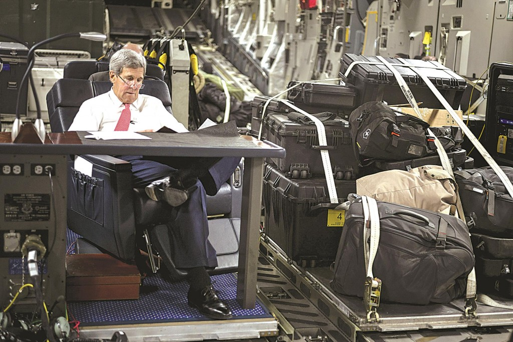 Secretary of State John Kerry on Wednesday reads on a flight en route to Iraq. (AP Photo/Brendan Smialowski)