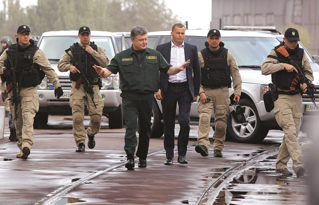 Surrounded by bodyguards, Ukrainian President Petro Poroshenko, center, walks during his visit to the Ilich Iron and Steel Works in the southern coastal town of Mariupol, Ukraine, Monday,  (AP Photo/Sergei Grits)