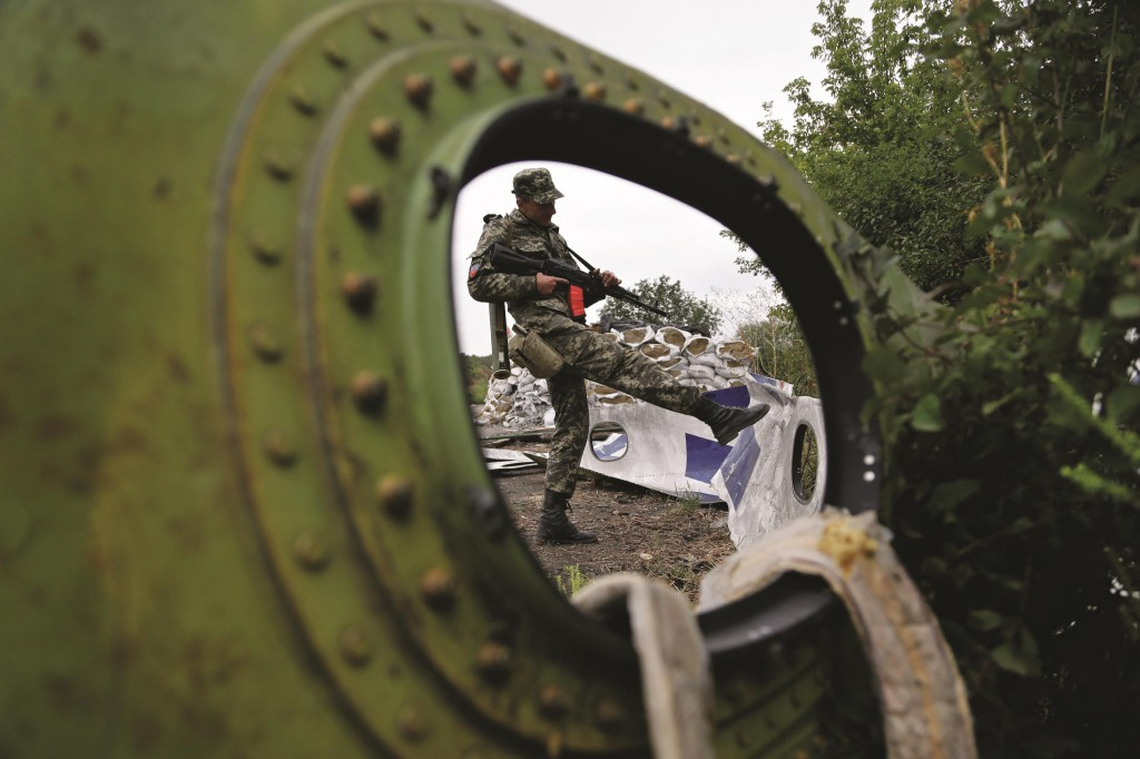 A Pro-Russian rebel looks at pieces of the Malaysia Airlines Flight 17 plane near village of Rozsypne, eastern Ukraine, Tuesday. (AP Photo/Sergei Grits)