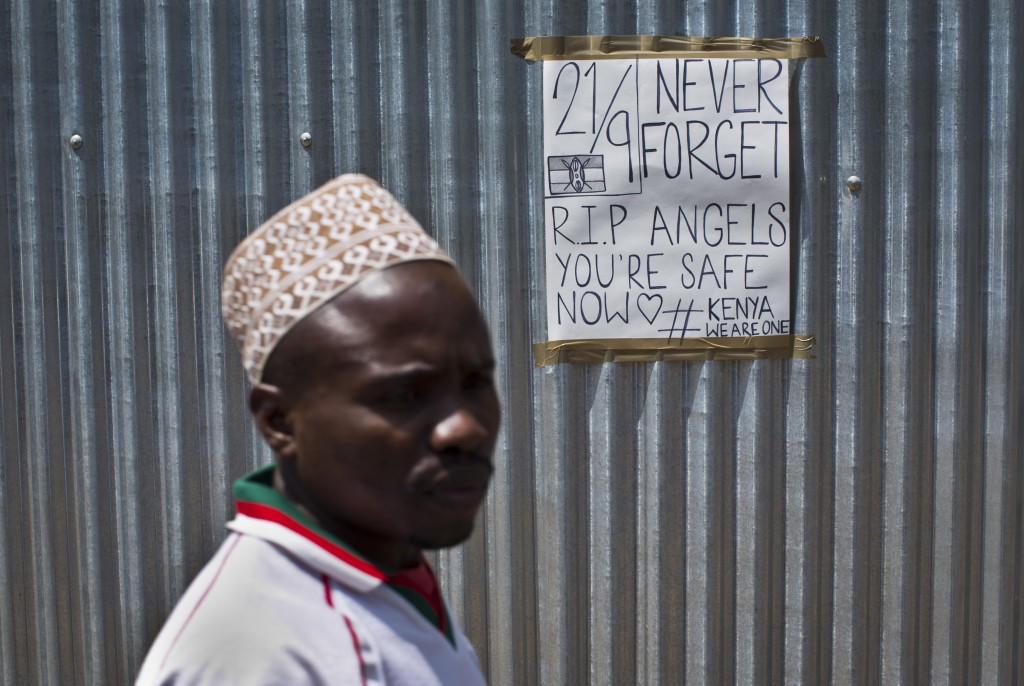 A man walks past a sign put up in memory of the victims of the Westgate Mall attack, on a metal fence outside the still-closed mall in Nairobi, Kenya, on Sunday.  (AP Photo/Ben Curtis)