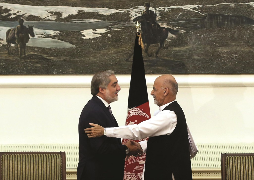 Afghanistan's presidential election candidates Abdullah Abdullah (L) and Ashraf Ghani Ahmadzai (R) shake hands after signing a power-sharing deal at the presidential palace in Kabul, Afghanistan, on Sunday. (AP Photo/Massoud Hossaini)