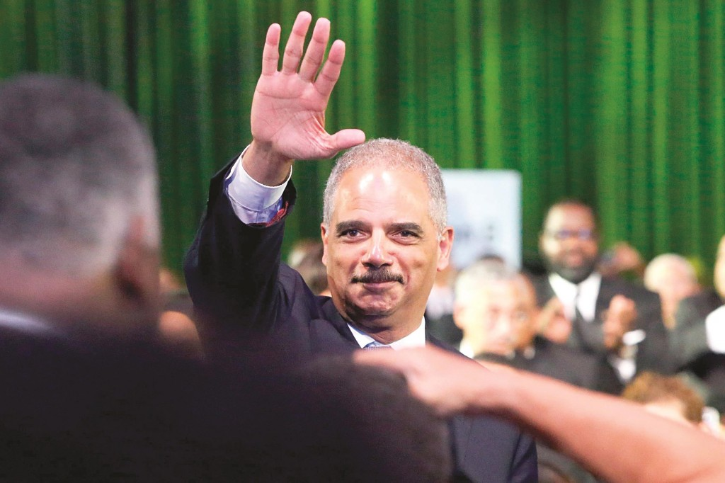 U.S. Attorney General Eric Holder returns an acknowledgement from President Barack Obama at the Congressional Black Caucus Foundation dinner in Washington on Saturday. (REUTERS/Jonathan Ernst)